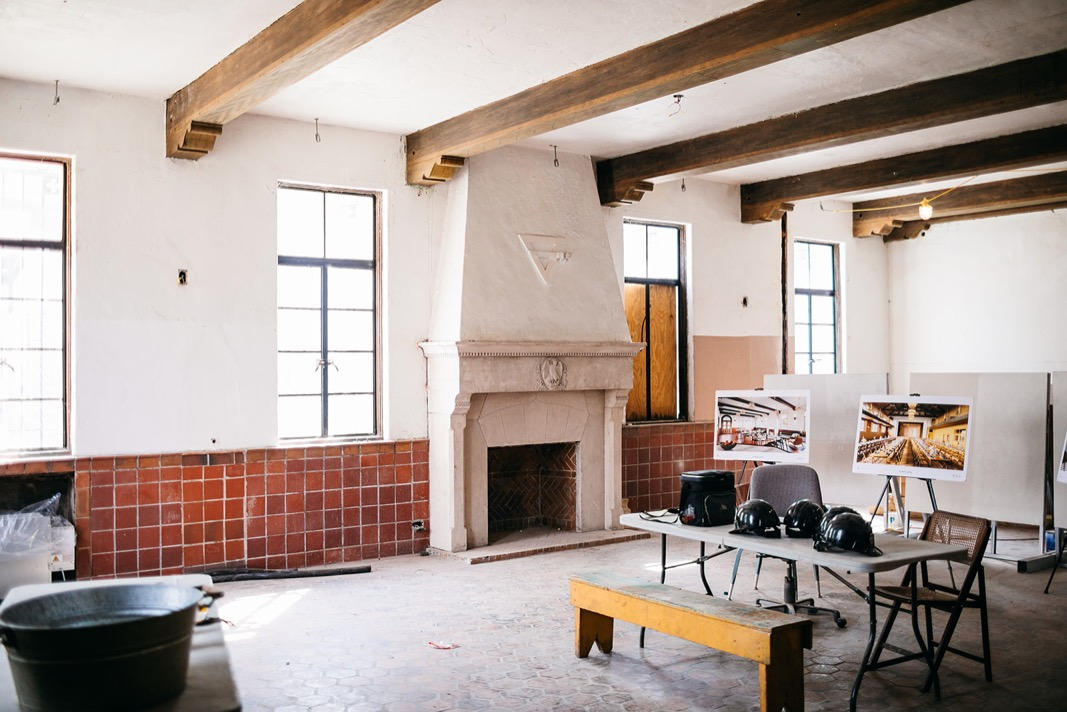 folding table holding hard hats in Common House Chattanooga Pennybacker Room. antique red tiles line the walls near fireplace