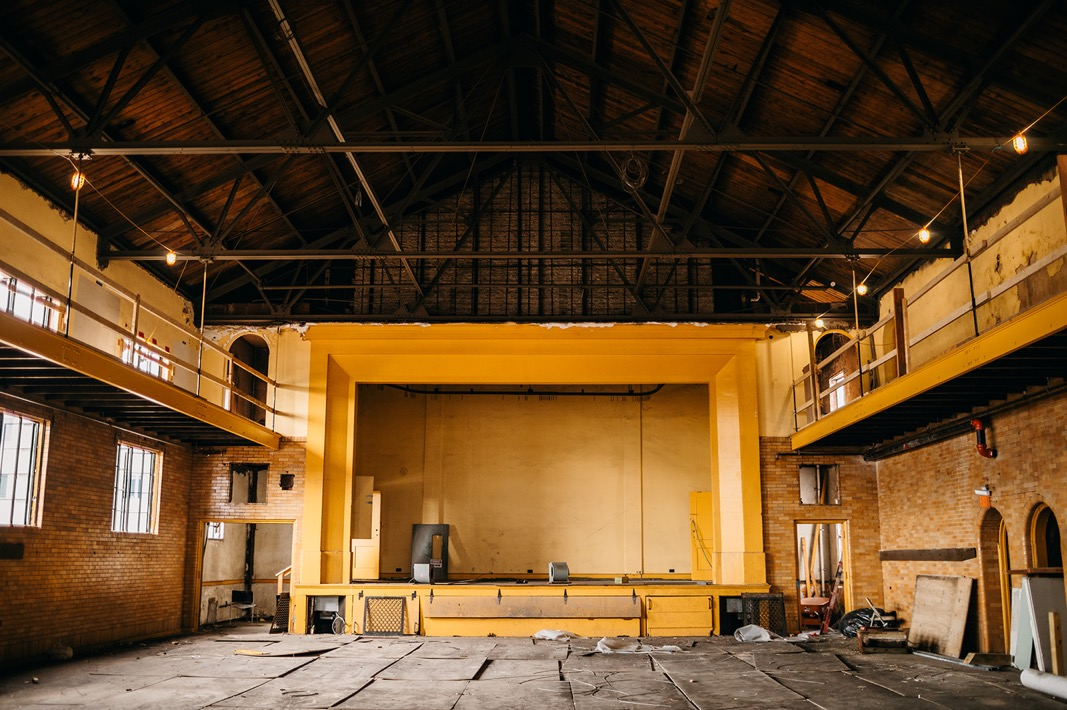 high peaked ceiling and open rafters of Common House Chattanooga's Ruby Hall with stage, brick walls, and catwalk balconies