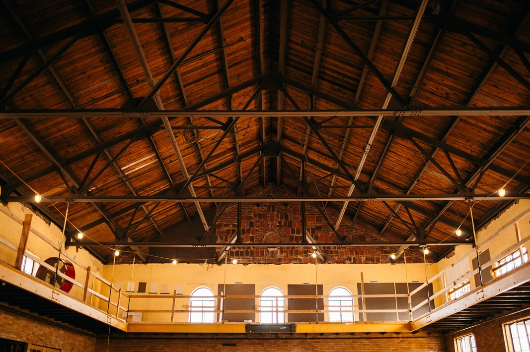 high peaked ceiling, open rafters, and arched upper windows along catwalk balcony of Common House Chattanooga's Ruby Hall