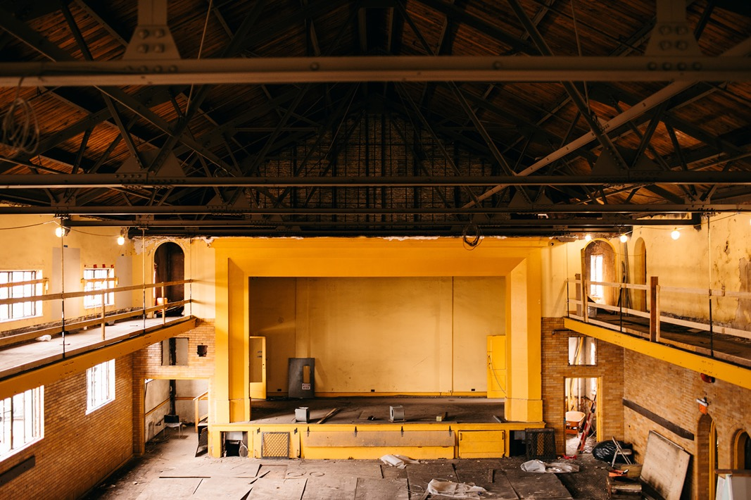 open rafters and yellow-painted stage of Common House Chattanooga's Ruby Hall with brick walls and catwalk balconies