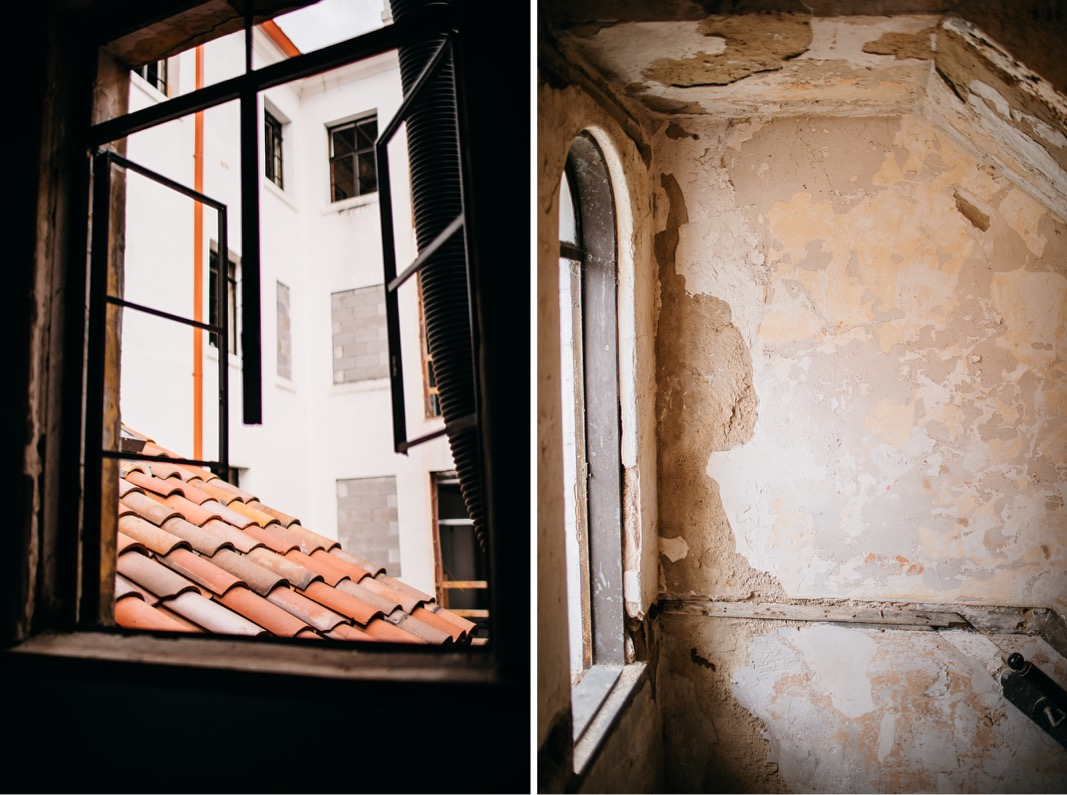 rough plastered walls in stairwell leading to rooftop patio and window view of Spanish tile roof