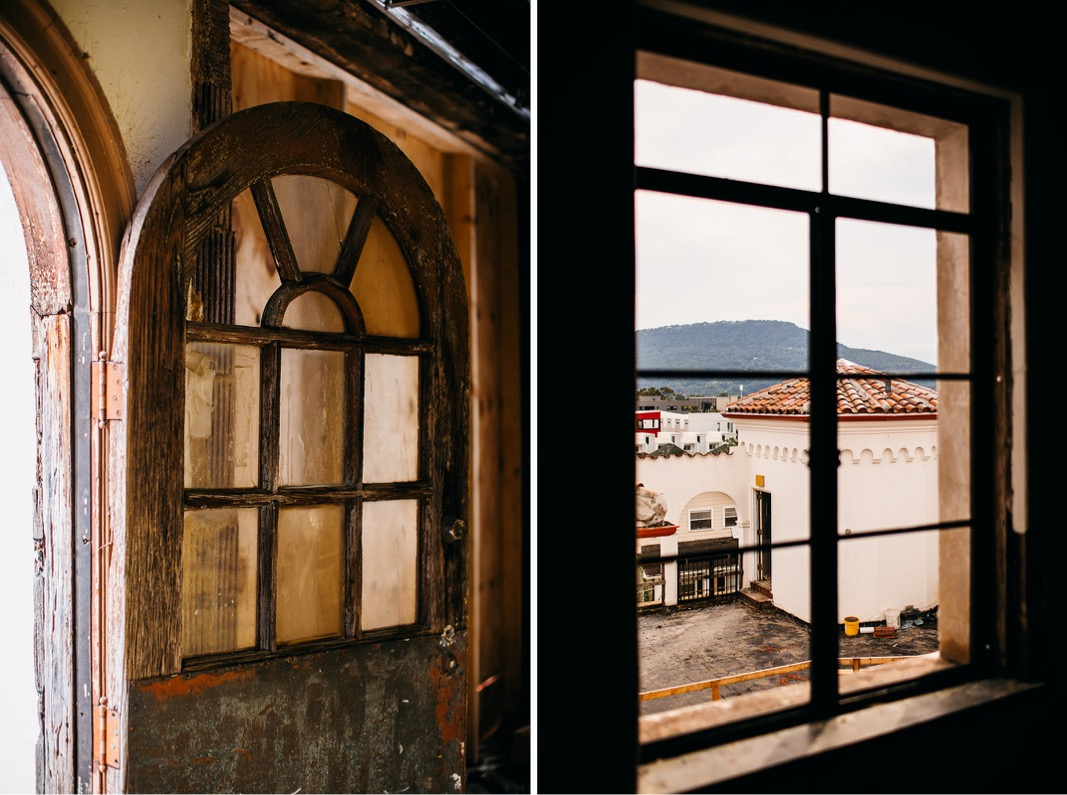 old, arched wooden door overlooking rooftop patio space and Spanish tile roof