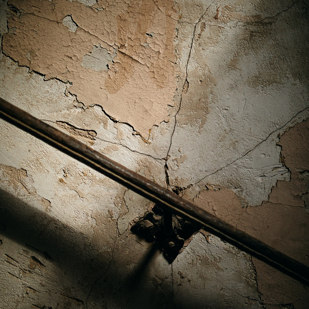 cracked plaster walls and peeling paint behind an iron railing