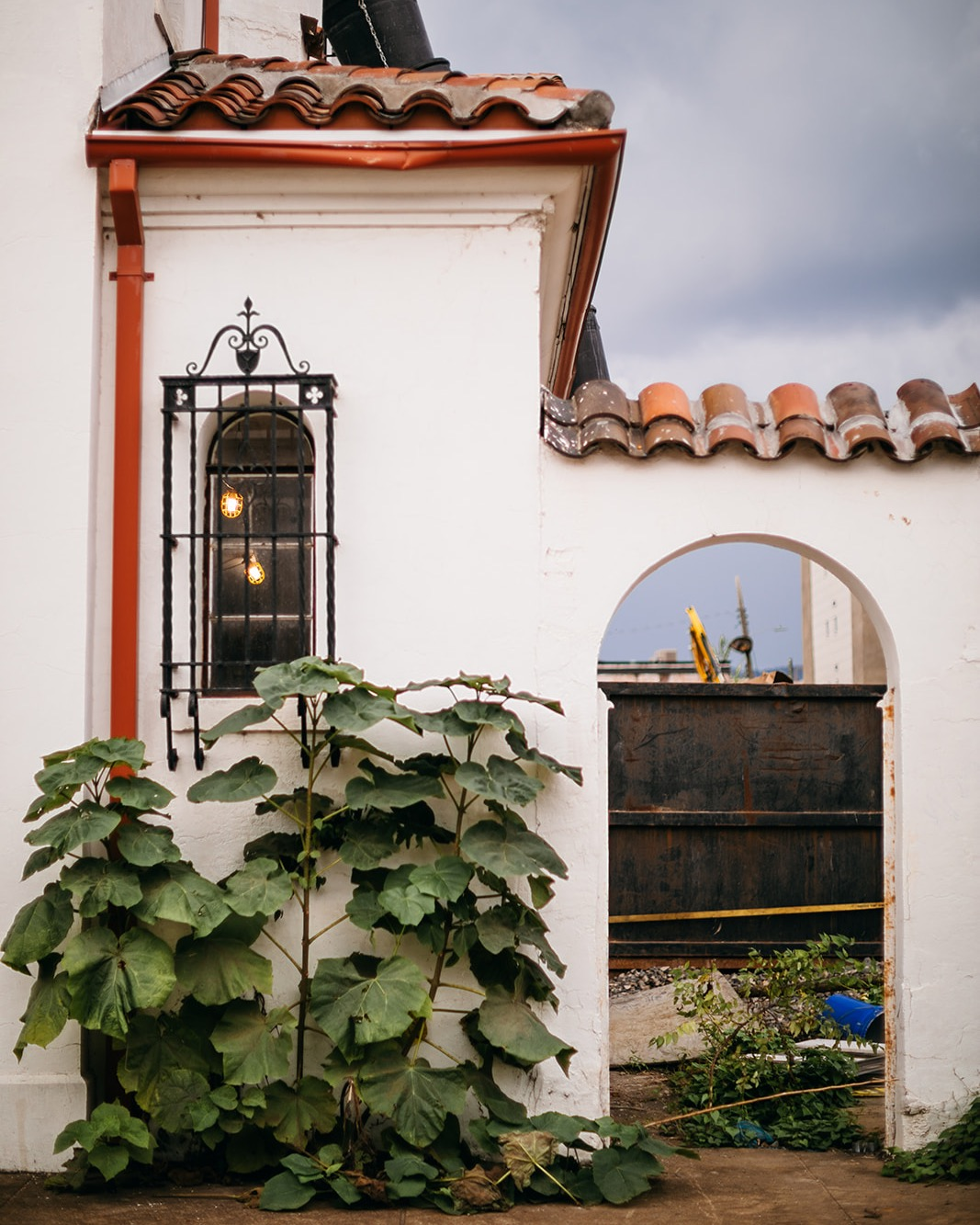 whitewashed exterior of Common House Chattanooga with wrought iron window bars, red gutter downspouts and Spanish tile roof