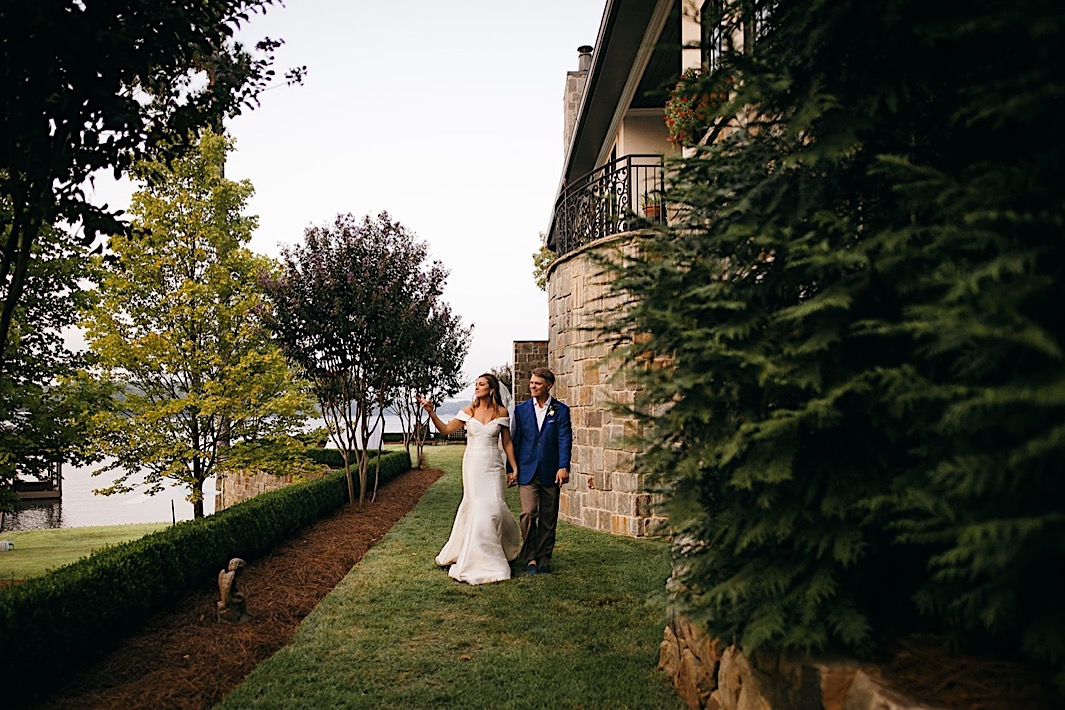 A bride and groom walk hand-in-hand on a landscaped lawn next to a stone wall.