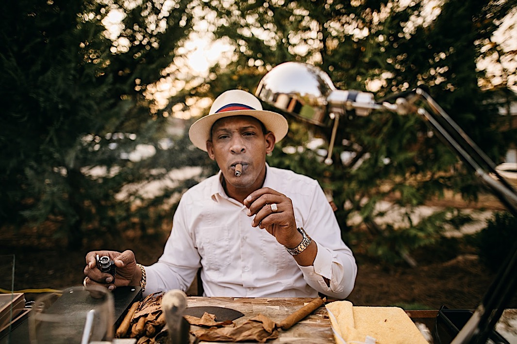 A cigar maker smokes a cigar at a table on a landscaped lawn.