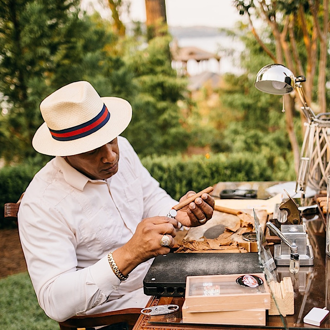 A cigar maker rolls a cigar at a table on a landscaped lawn.