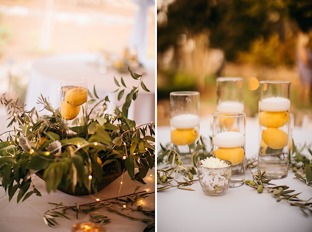 Floating candles in vases with lemons surrounded by olive branches and twinkle lights.