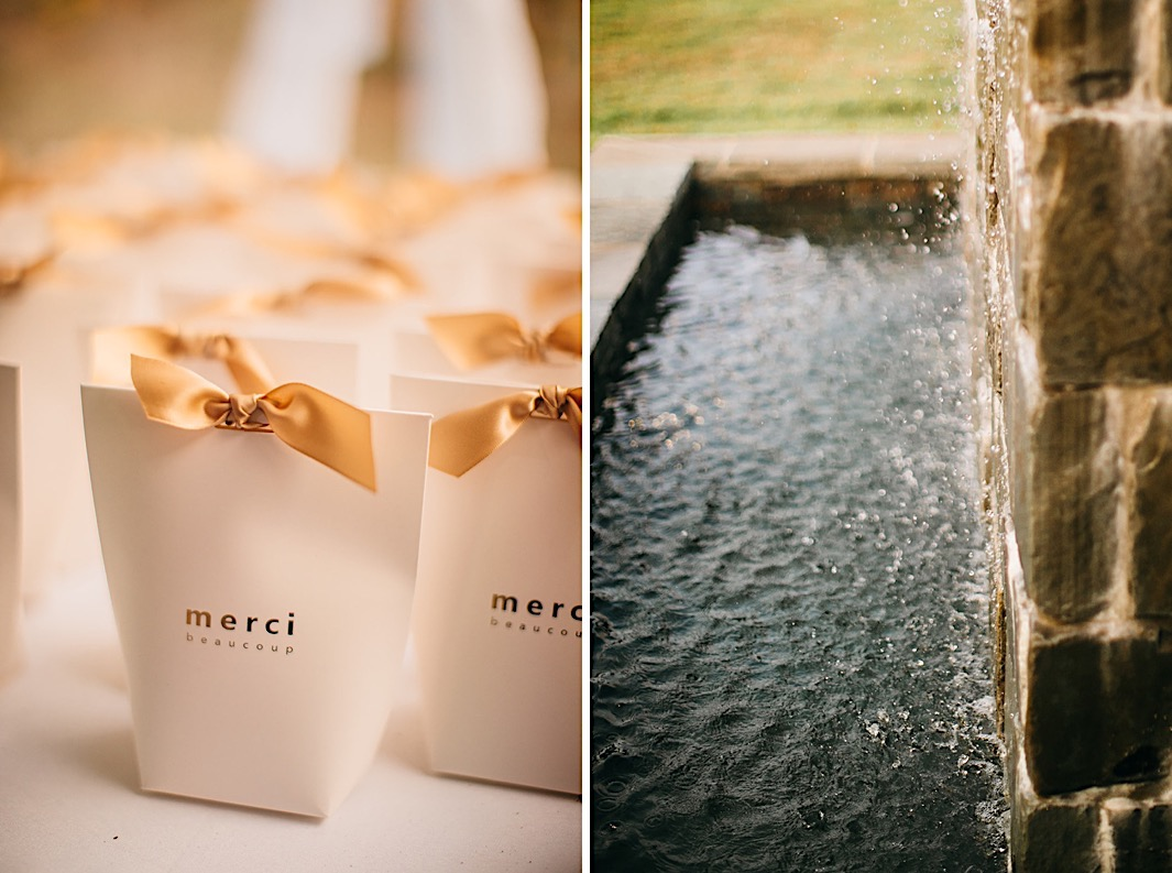 Wedding favors in white bags with golden bows. A stone fountain trickles in a backyard.