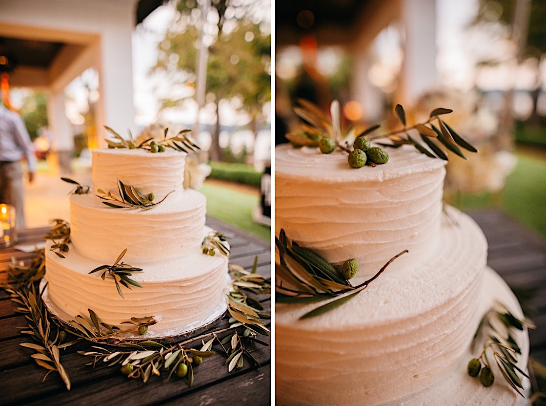 A three-tiered white wedding cake adorned with olive branches.