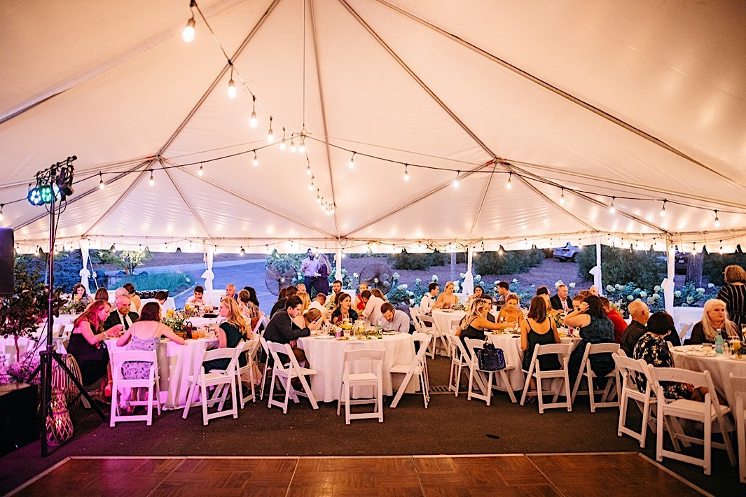 Wedding guests dine beneath a white tent at a big backyard wedding.