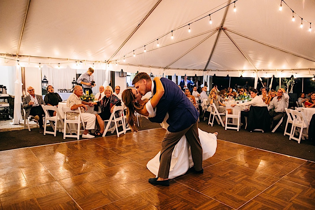 A groom dips his bride on the dancefloor while guests watch.