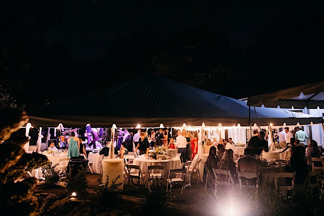 Wedding guests mingle beneath a lit canopy at night at a big backyard wedding.