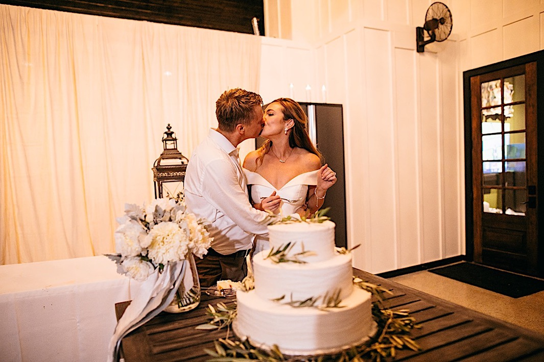 A bride and groom share a kiss next to their three-tier wedding cake.