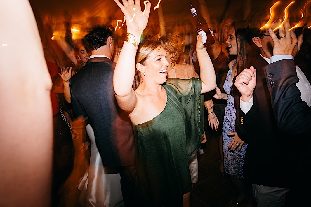 A woman dances with her hands in the air on a crowded dancefloor.