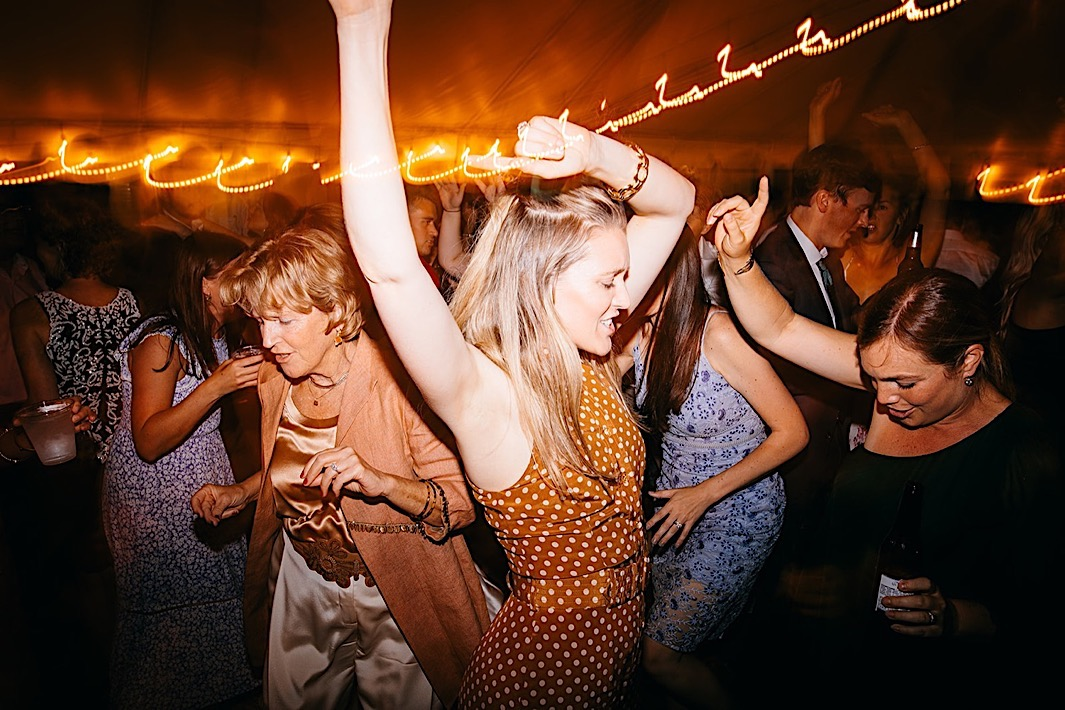 A woman dances with her arms in the air on a crowded dancefloor.