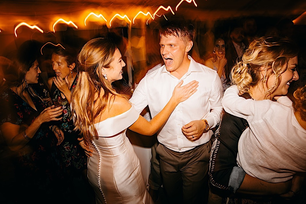 A bride and groom dance on a crowded dancefloor.
