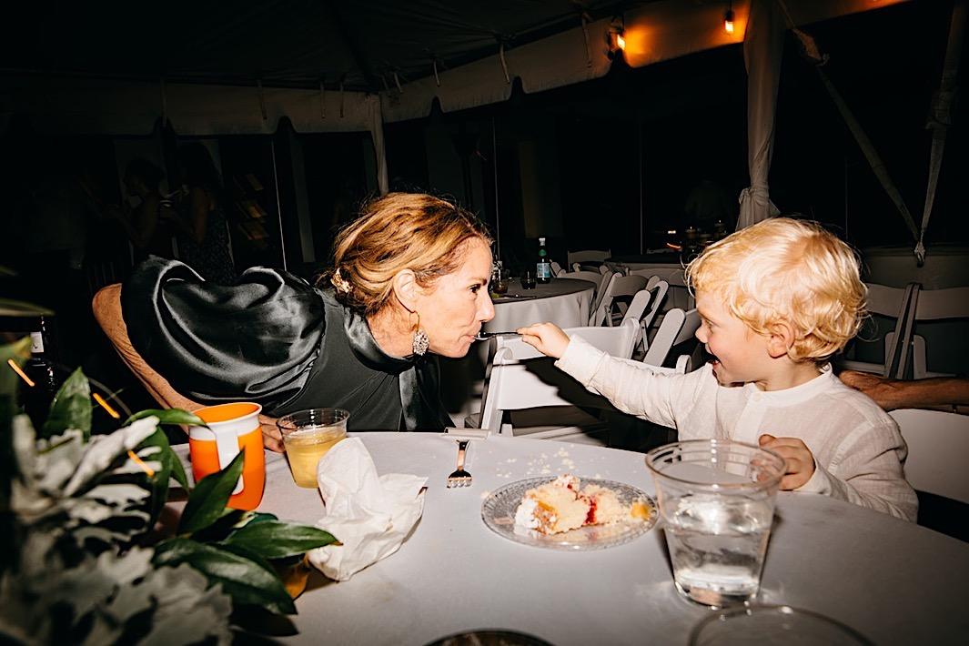 A little boy feeds a woman a bite of dessert at a big backyard wedding.