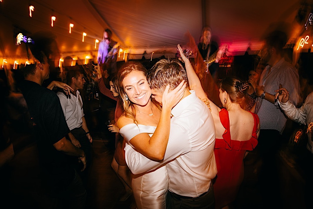 A bride and groom smile while holding each other on the dance floor.