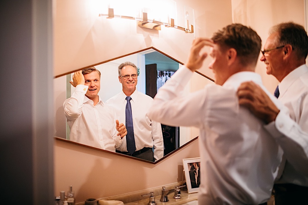 A groom fixes his hair in a mirror while his father-in-law watches.