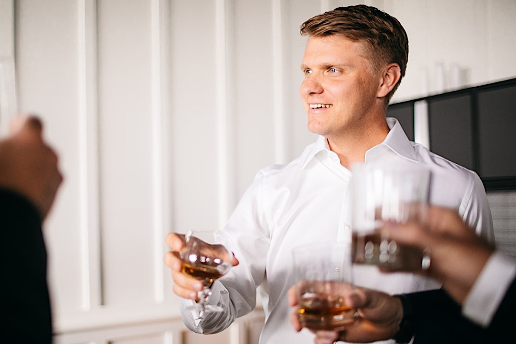 A groom toasts with a dram of whiskey.