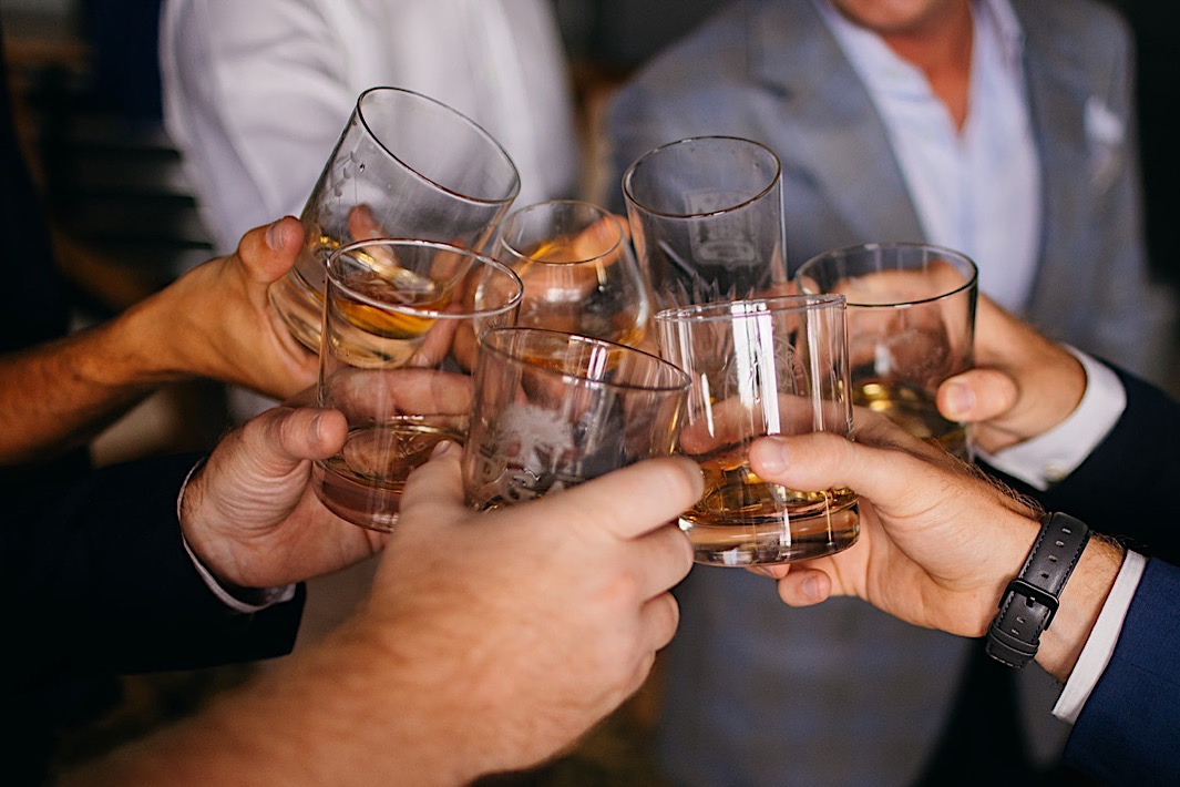 Men cheers with drams of whiskey.