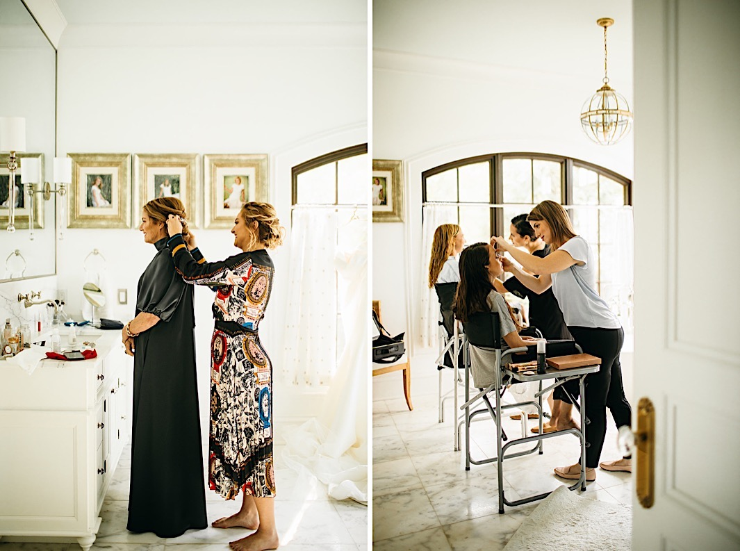 Women fix each others' hair in front of a large mirror.