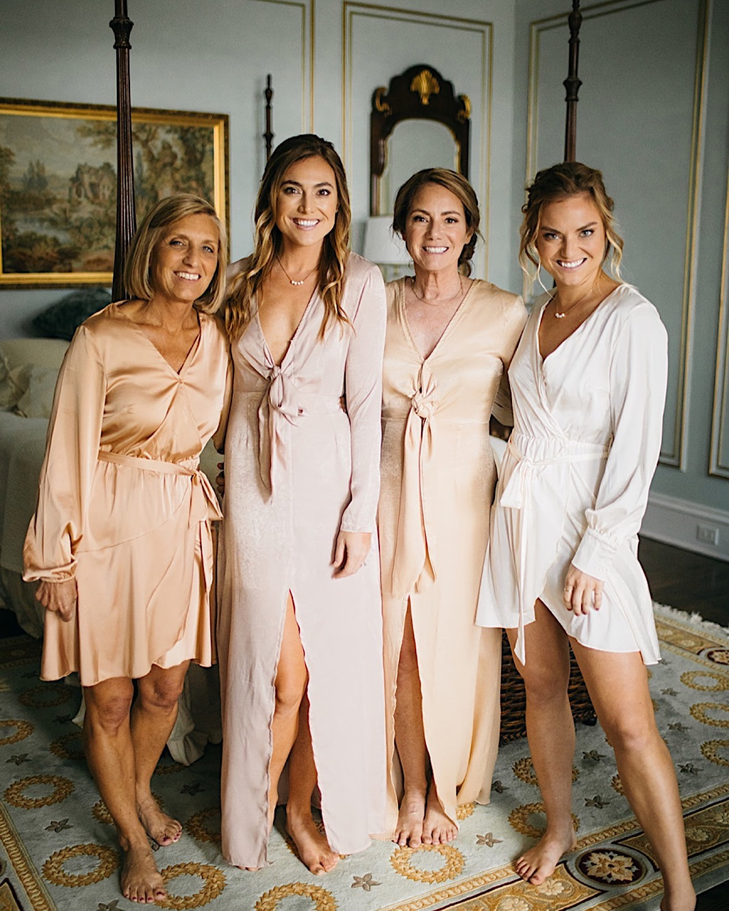 A bride and her bridal party pose in peach dressing gowns.