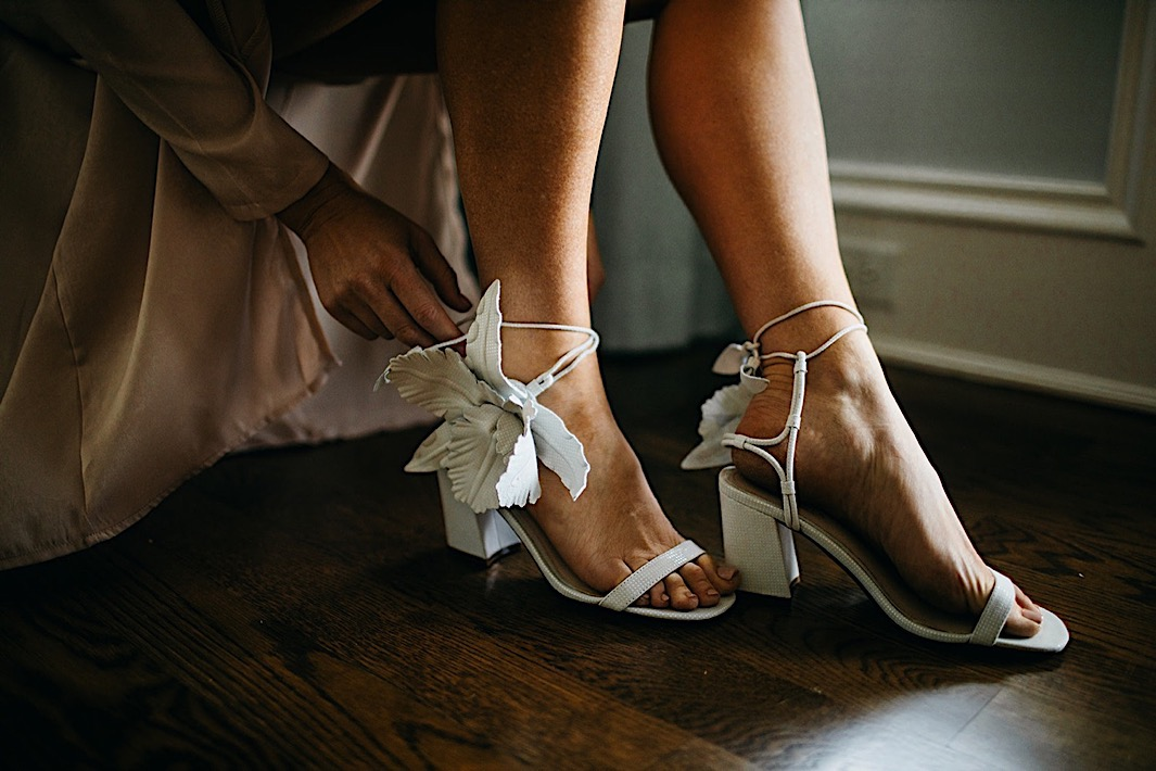 A bride fastens the closure on her powder blue wedding shoes.