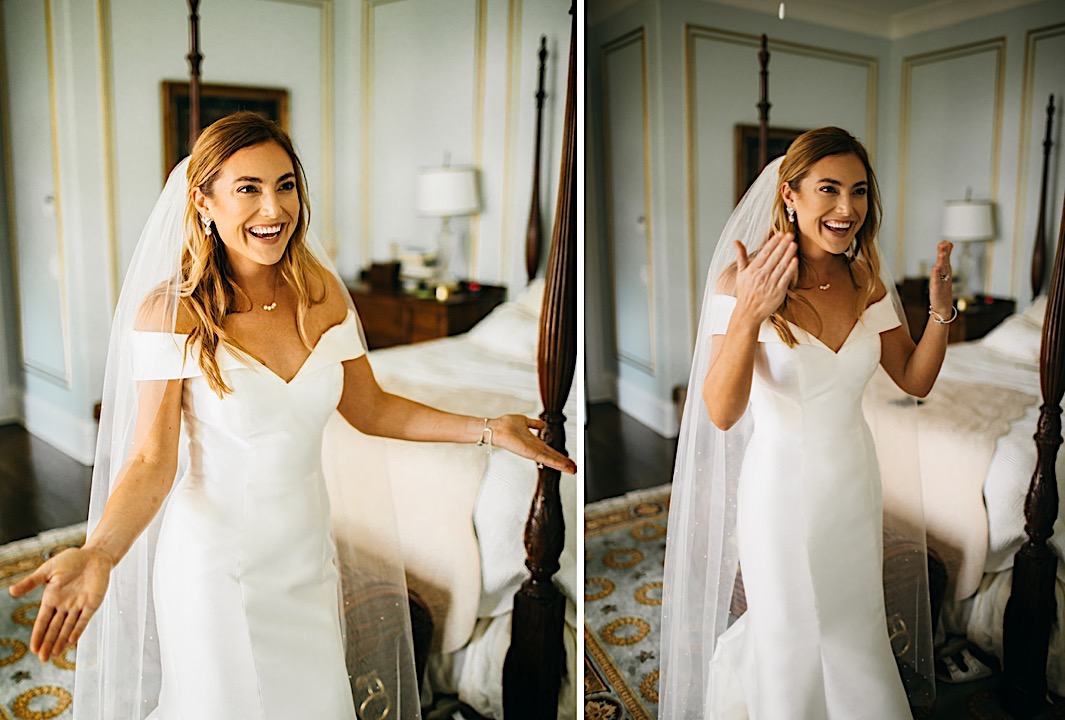 A bride smiles and shows off her wedding gown in the dressing room.