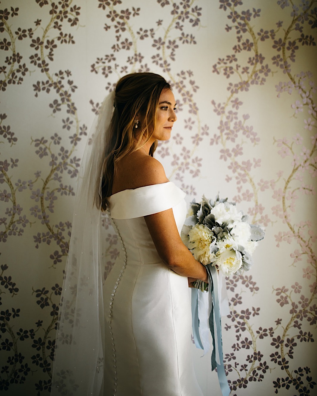 A bride poses with her blue and white bouquet in front on a floral wallpapered wall.