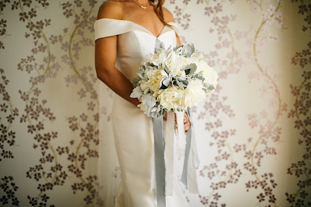A bride holds a white and baby blue bouquet in front of a floral wallpapered wall.