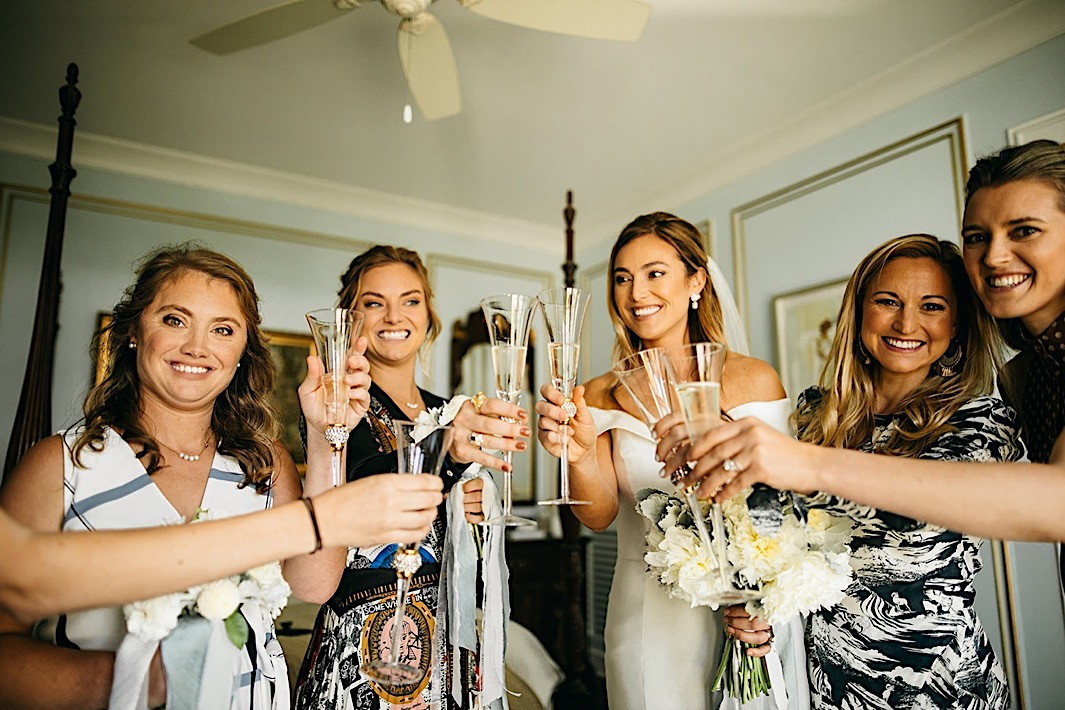 The bridal party and bride cheers with champagne flutes.