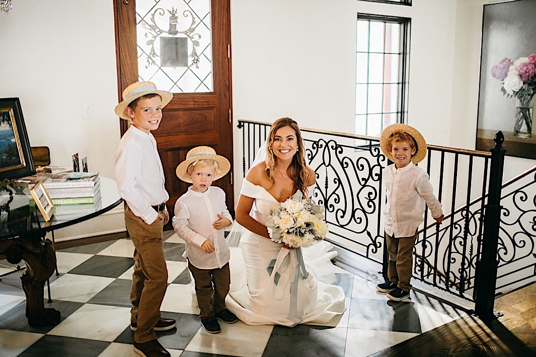 A bride poses at the top of a staircase with her three ring bearers.
