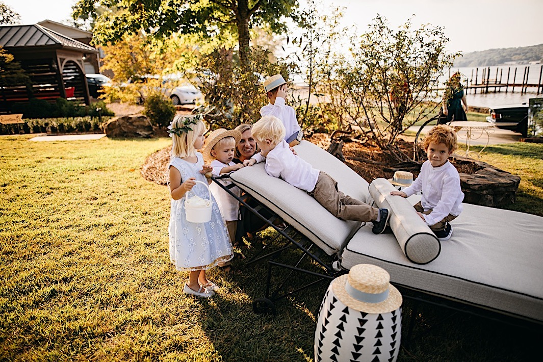 Ring bearers and flower girl play on a chaise on the lawn.