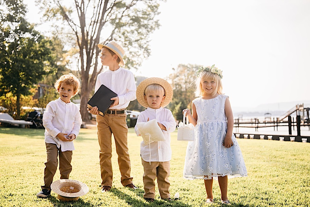 Three ring bearers wearing white shirts and straw hats. A flower girl wearing a light blue dress and a flower crown.