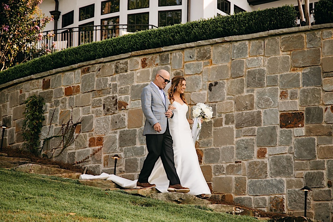 A bride and her father walk together down stone steps towards the altar.