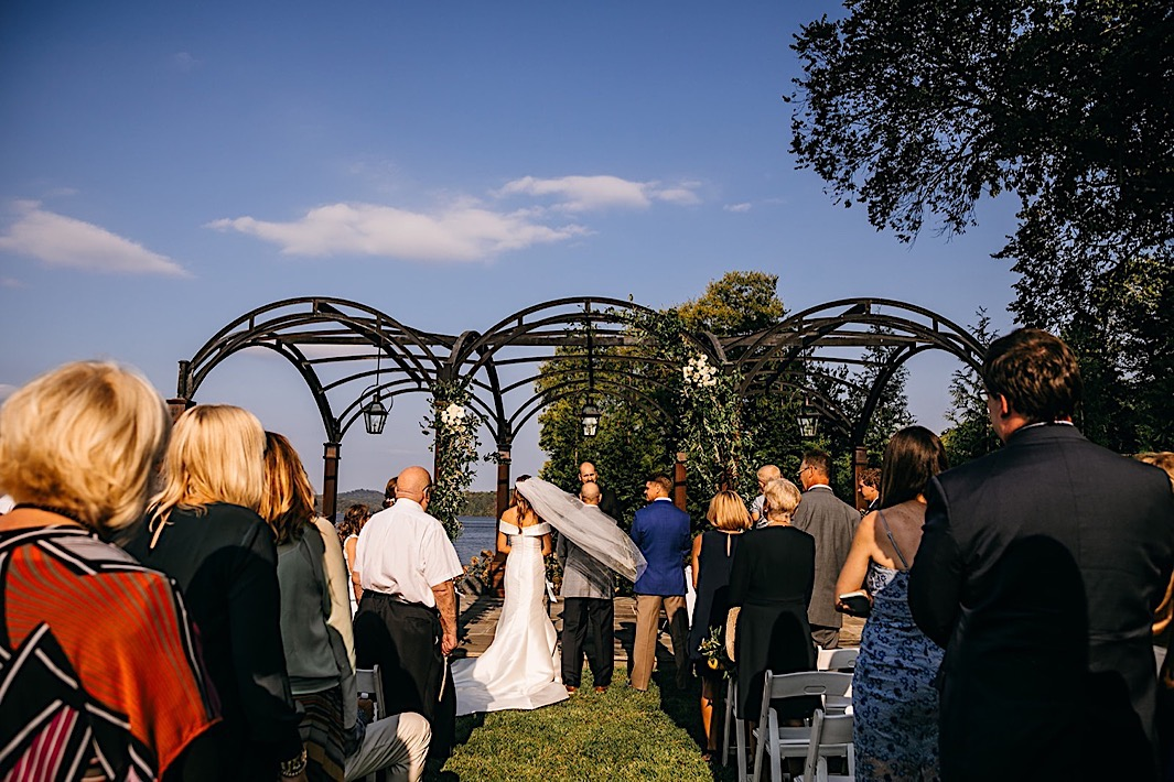 A father gives away the bride at a big backyard wedding.