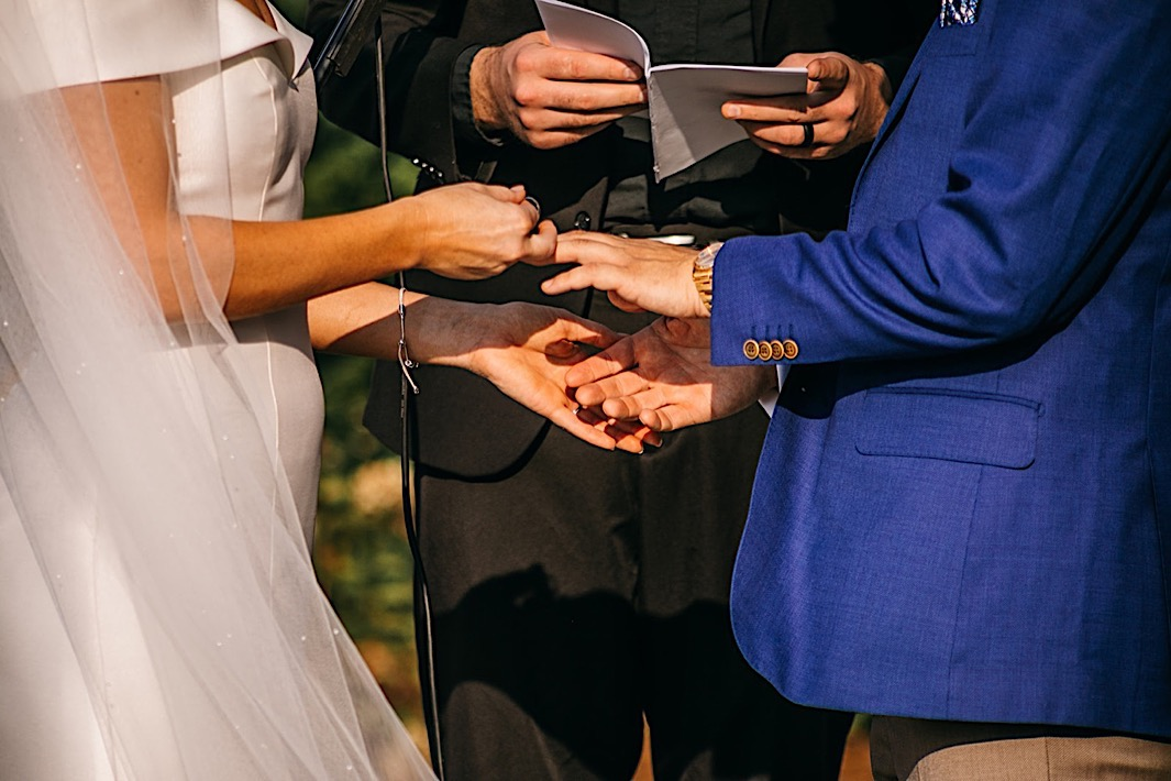 A bride and groom exchange rings at their big backyard wedding.