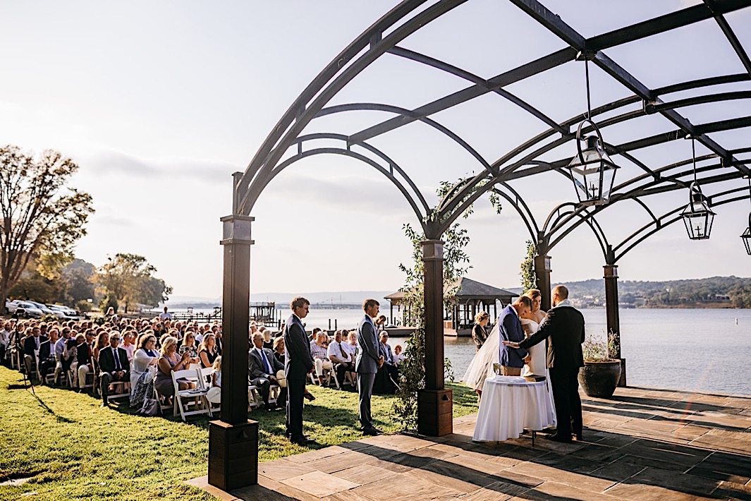 A bride and groom stand at the altar in front of their wedding guests.