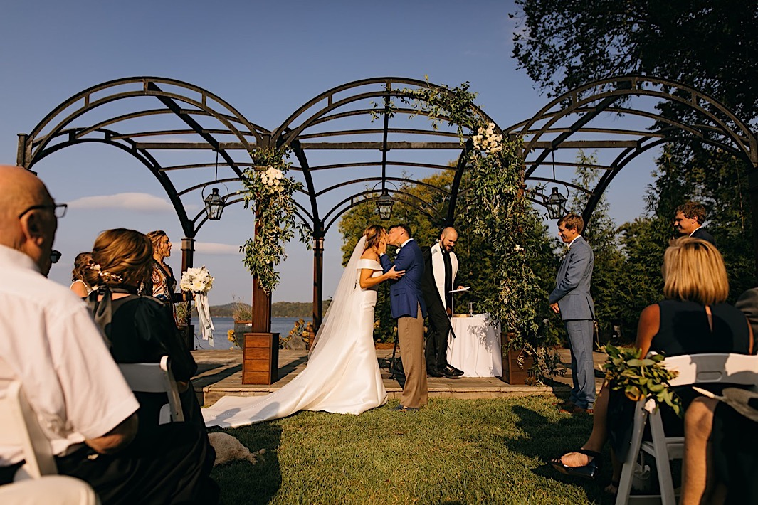 A bride and groom kiss at the altar at their big backyard wedding.