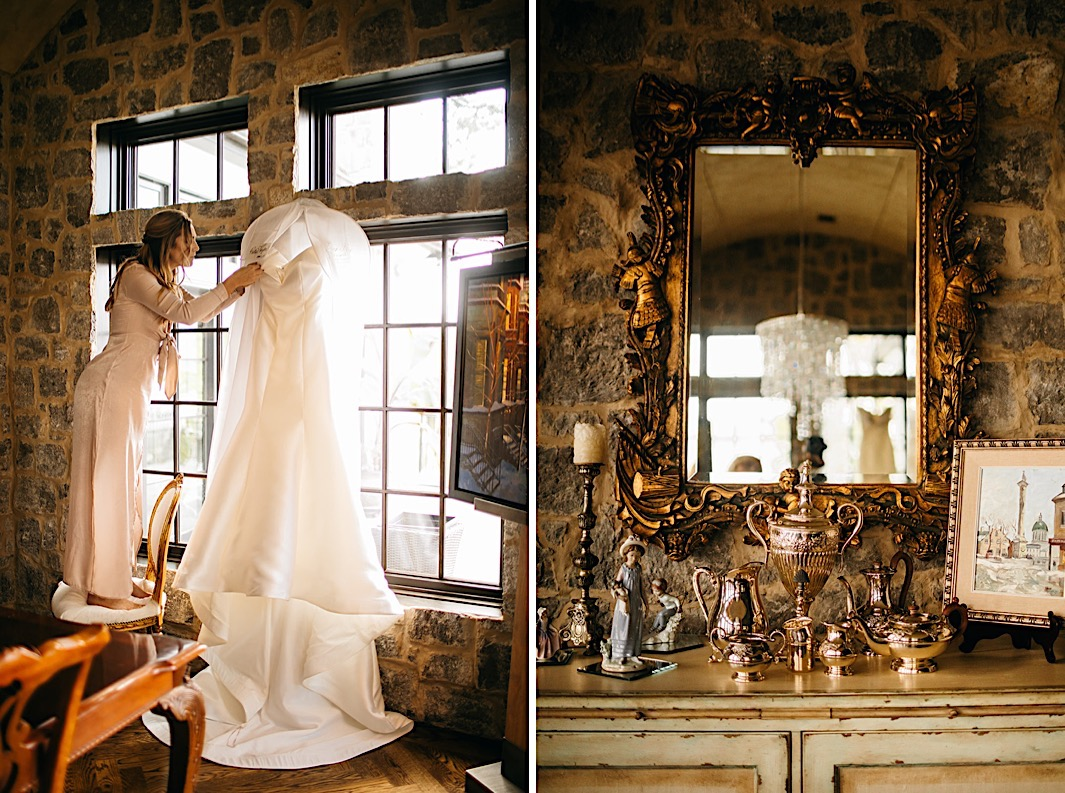 A woman adjusts a wedding dress hanging in front of a large window in a stone dining room.