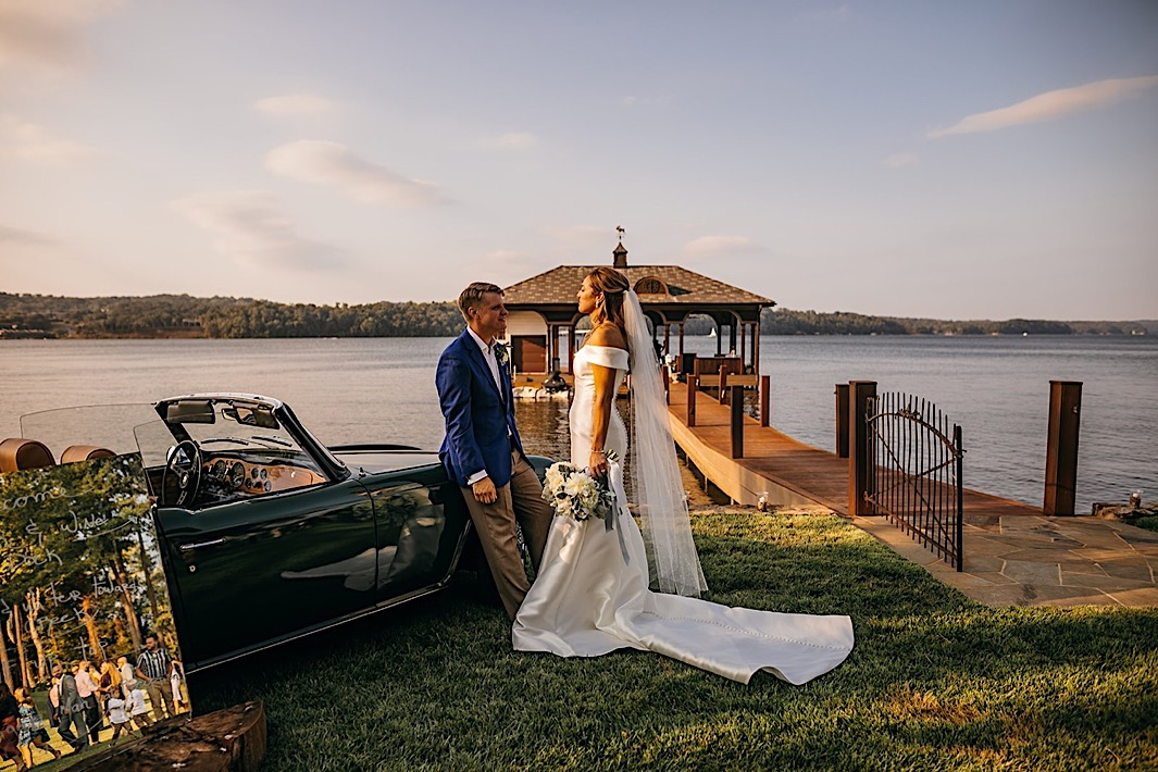 A bride and groom chat next to a vintage car parked on a lake.