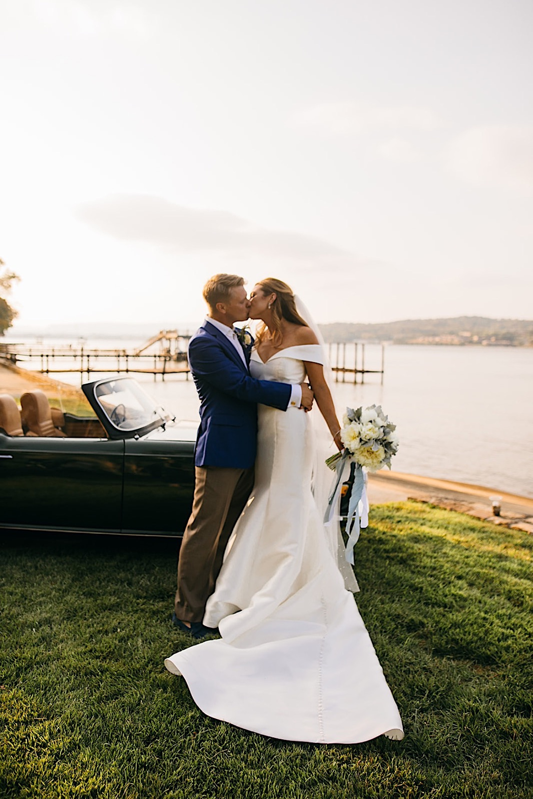 A bride and groom kiss in front of a vintage car parked by a lake.