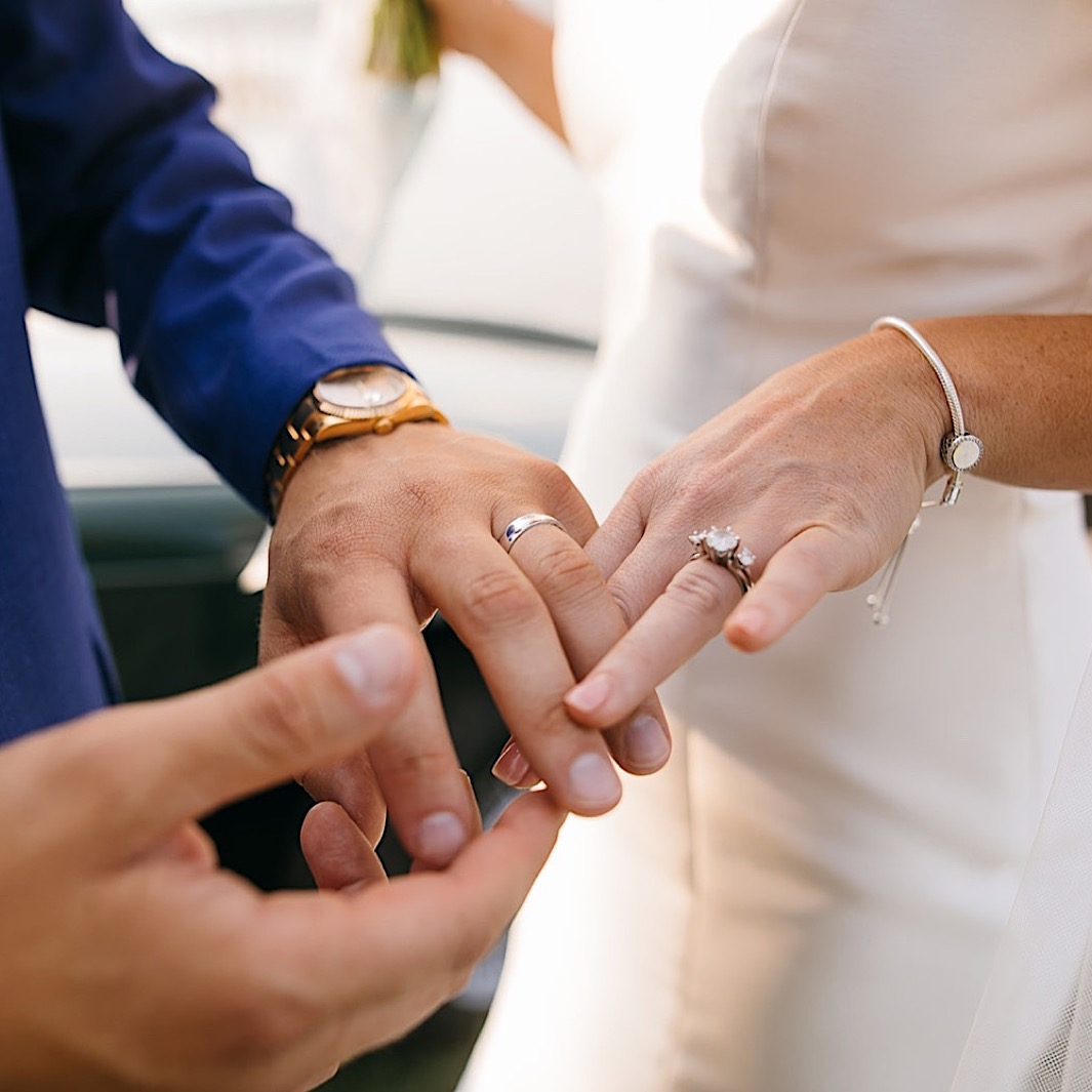 A bride and groom admire their new wedding rings.