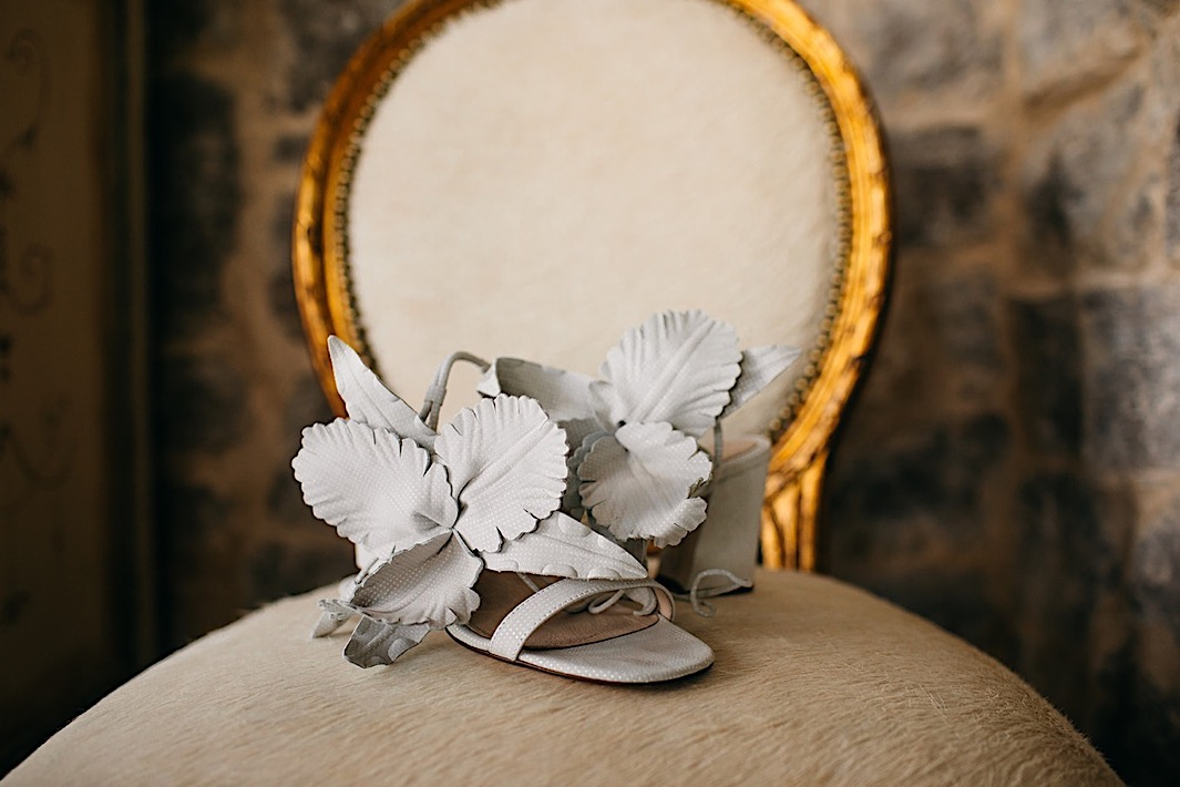 A pair of light blue shoes with suede flowers displayed on an antique gold and cream chair.
