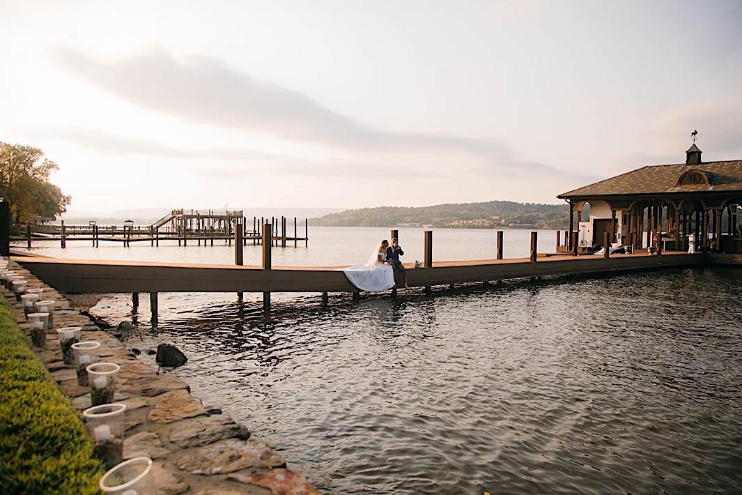 A bride and groom sit side-by-side on a dock at sunset.