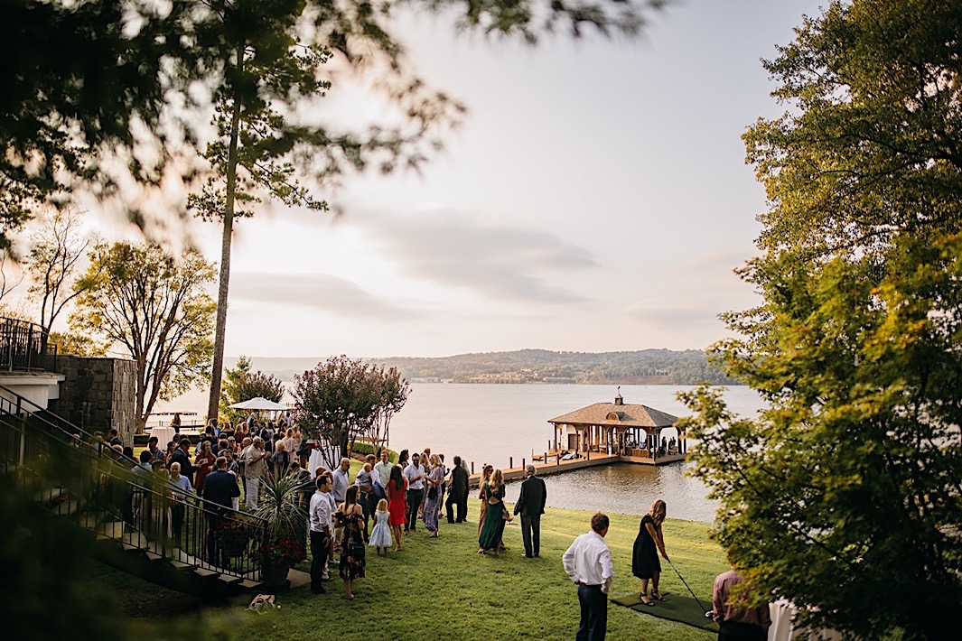 Wedding guests mingle on a lawn overlooking a lake.