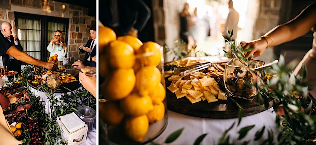 Wedding guests reach for a charcuterie board surrounded by lemons and olive branches.