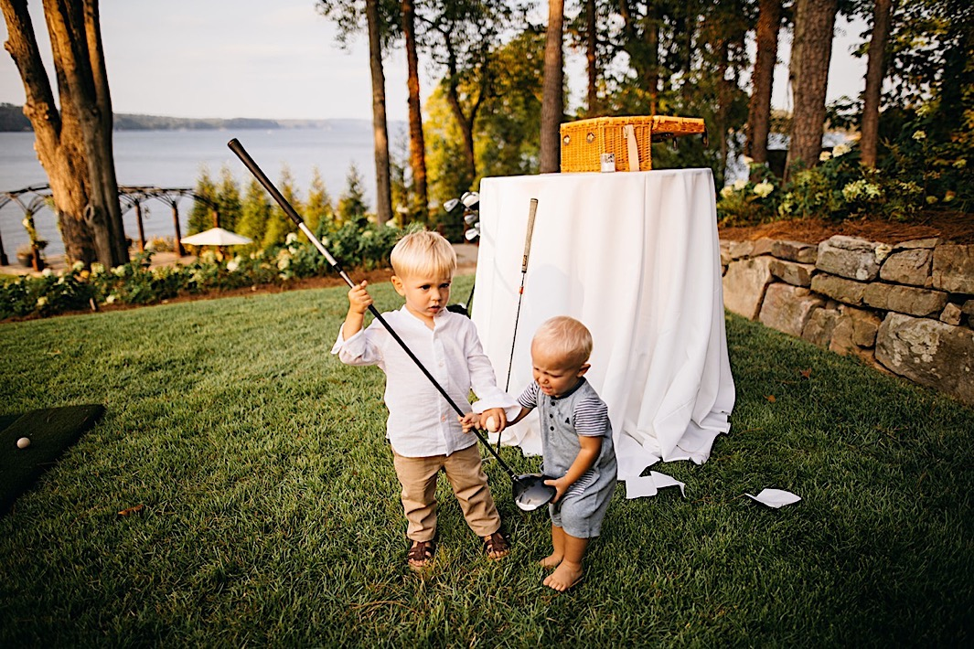 Two little boys play with golf clubs on a manicured lawn near a lake.